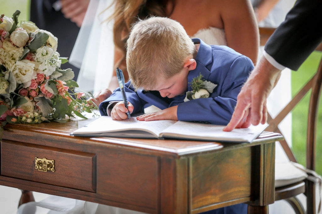 little boy signing paper at wedding