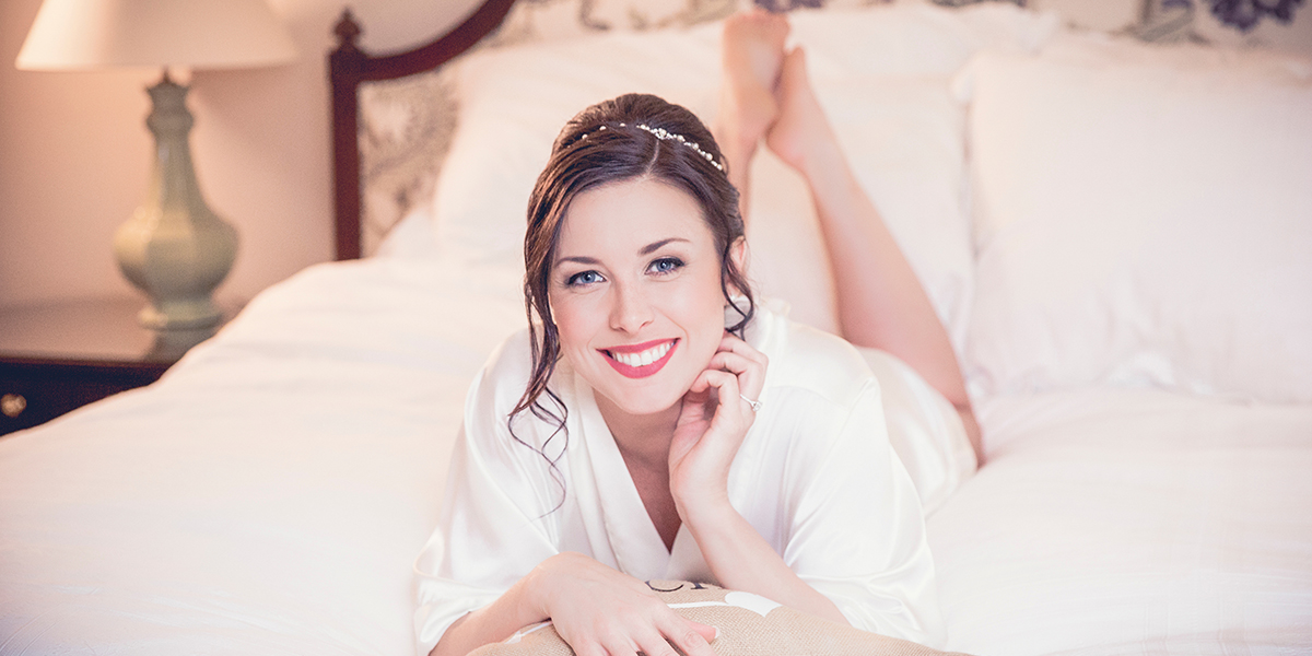 bride smiling on bed