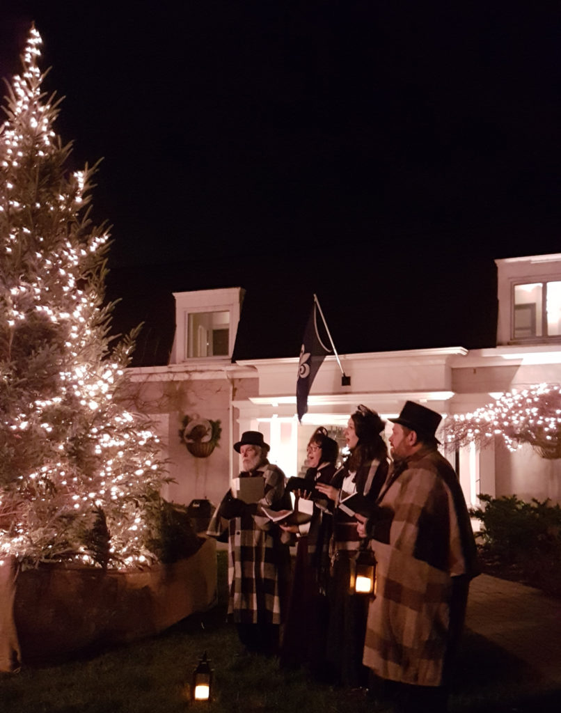 carolers beside a tree
