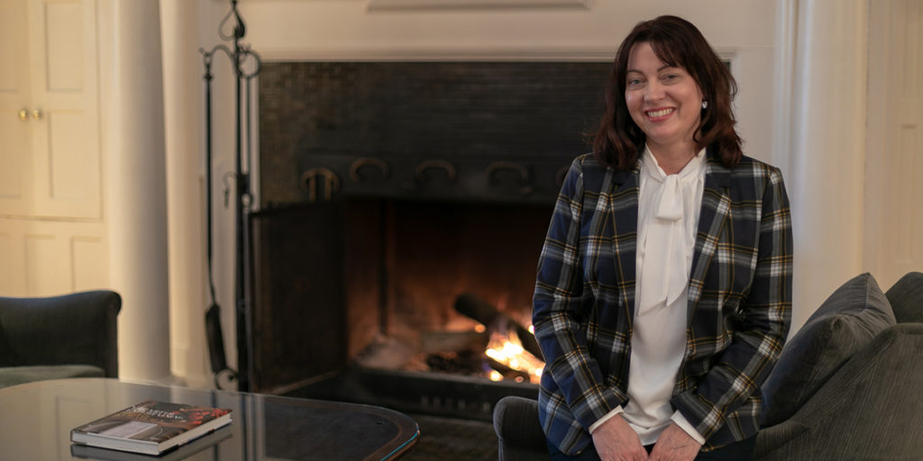 Jodi sitting in front of fireplace