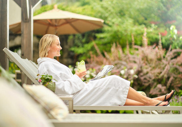 Guest in robe, with drink using the pool loungers