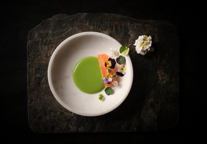 salmon with floral garnish, green veloute and garden herbs served on a white plate