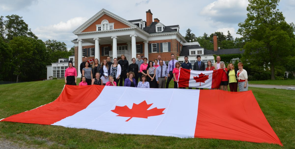 About 30 Langdon Hall employees on the front lawn outside of the Main House, with Canadian Flags on Canada Day