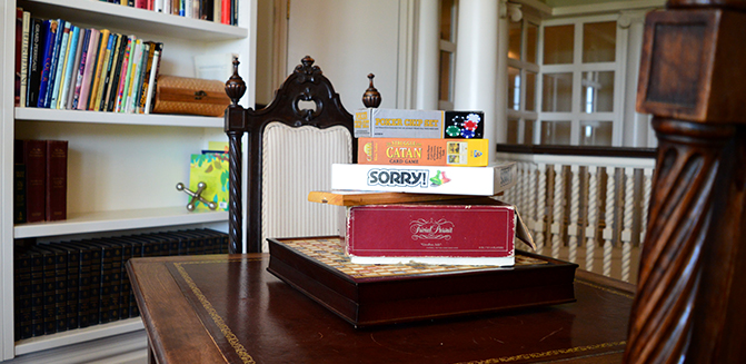 Games table with Scrabble, Trivial Pursuit, Sorry, Catan, and Poker on the table, set with two chairs and books in the background