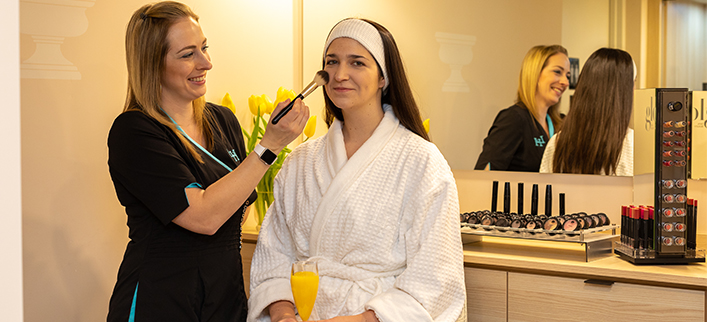 Guest getting a Makeup Application and enjoying a mimosa by Esthetician
