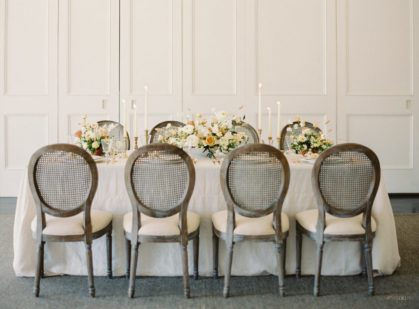 table decorated for a wedding with eight chairs