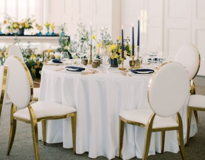 table set with wedding decor and florals with four gold and white chairs