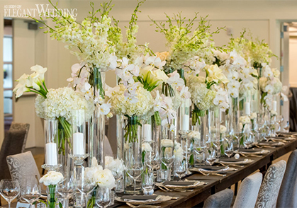 Wedding table set up with white florals, vases and candles on a harvest table
