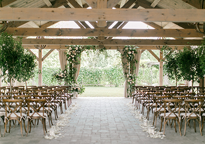 Our covered outdoor Summer House pavilion set up for a wedding ceremony with harvest chairs and green and white florals