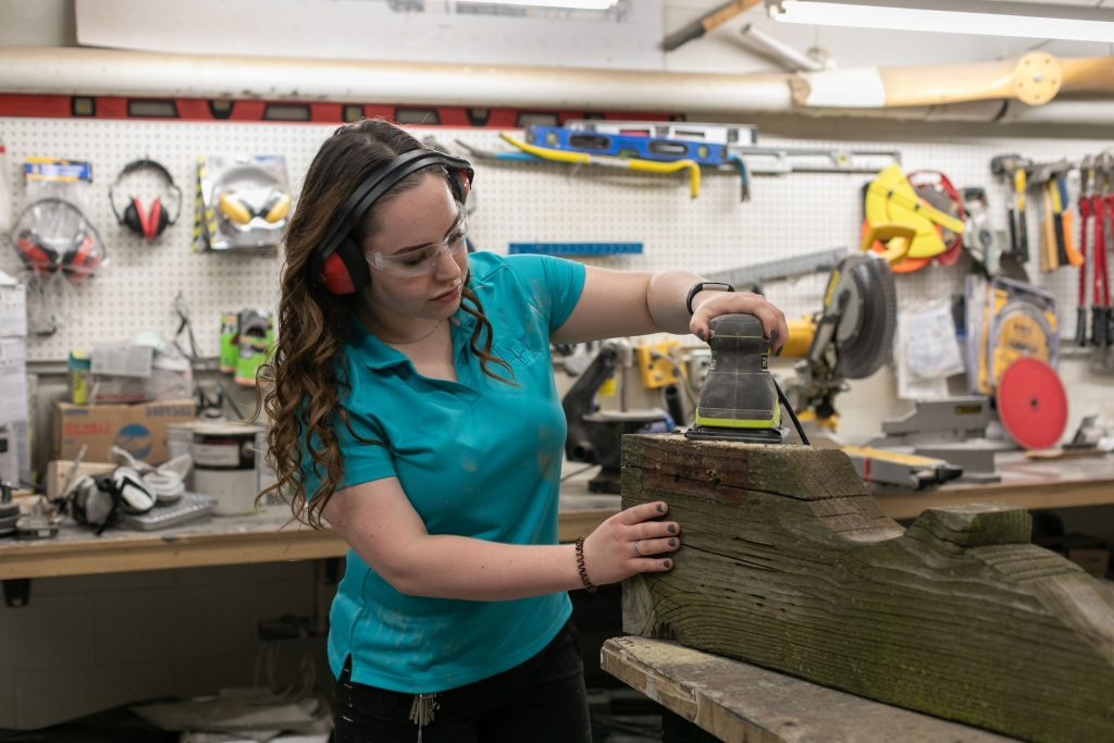 Brittney sanding and refinishing a piece of wood