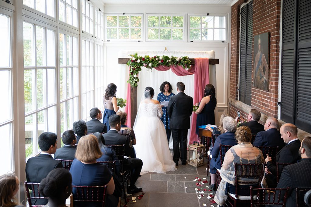Colonel Langdon's Ceremony with bride and groom, and guests with a pink curtain backdrop and florals