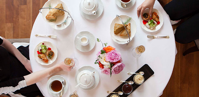 Aerial shot of two people having tea, with scones, preserves, and finger foods