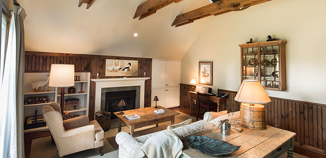 Interior shot of our Stable Suite, with couch, arm chair, table and map, fireplace and high ceilings