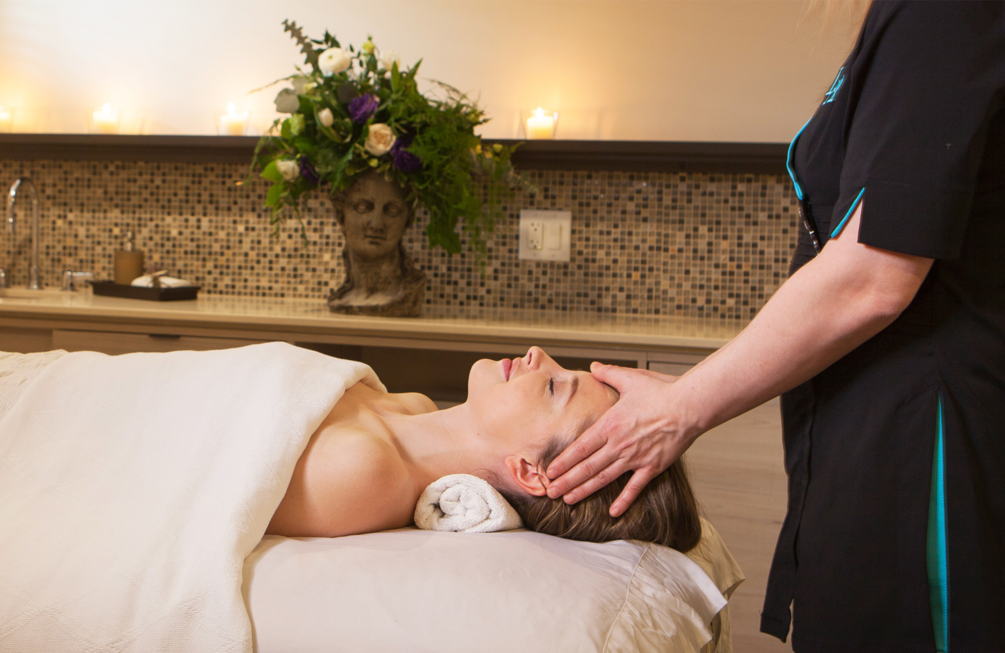 Woman receiving a relaxing facial massage by an esthetician