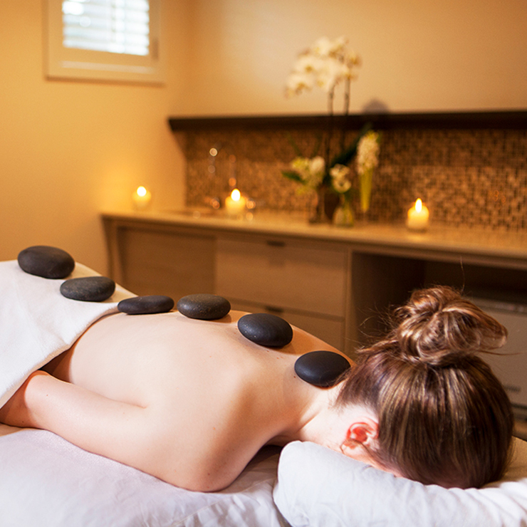 Lady face down with hot stones on her back for massage treatment