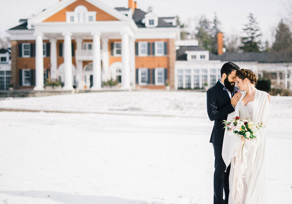 Bride and groom embracing in front of main house in the winter