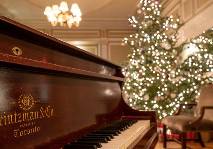 Close up of piano with decorated Christmas tree in the background