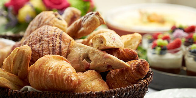 Pastry basket with fresh croissants and scones