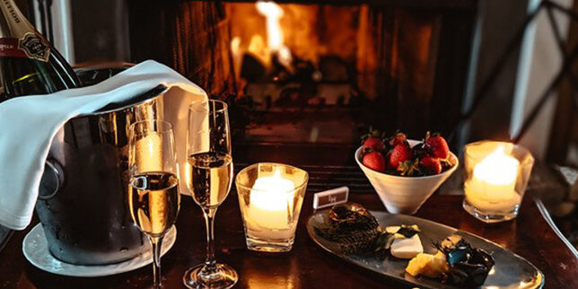 champagne with strawberries in front of fire